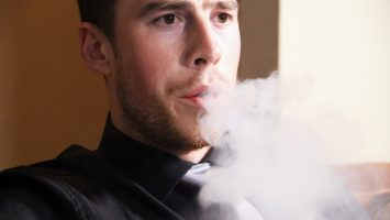 Ryan Billingham, 25, uses an electronic cigarette at his home in Columbus, Ohio. A new national survey shows 54% of men under age 35 think electronic cigarettes are less harmful to the lungs than cigarettes, but doctors aren`t sure.