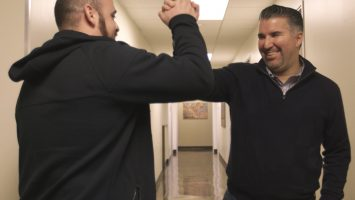 Basilio Santangelo (left) and Paul Diaz (right) high five as they pass in the hallway at The Men's Clinic at UCLA. Along with another friend, they made appointments to get vasectomies on the same day so they could recuperate together while watching sport