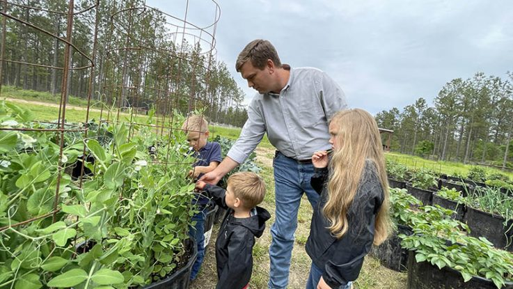 Travis Hammonds tends his garden with his children at their home in Alabama. Hammonds says donating their extra harvest to their local food bank helps fight food insecurity in their community and teaches his children the importance of giving back.